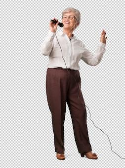 Seniorin mit vollem körper, glücklich und motiviert, singt ein lied mit einem mikrofon, präsentiert ein ereignis oder feiert eine party, genießt den moment