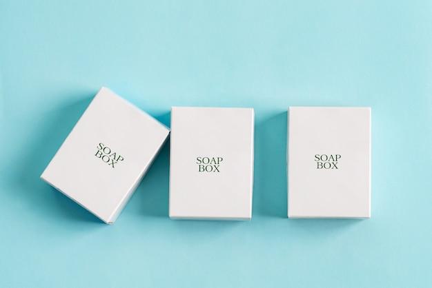Set aus drei papiermodellboxen zum verpacken von produkten und dingen auf pastellblauem hintergrund.
