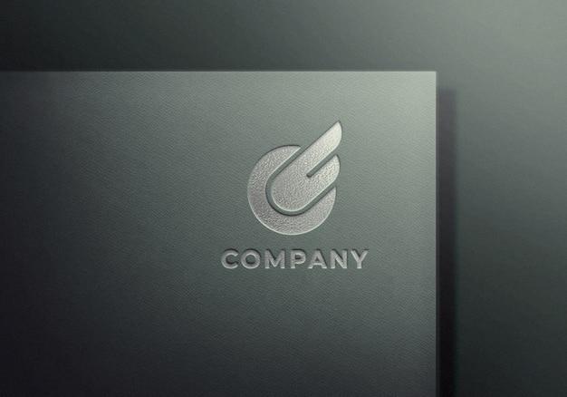 Silber geprägtes logo-modell auf grau strukturiertem papier