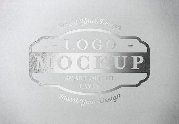 Silber gepresstes logo mockup auf weißbuchbeschaffenheit