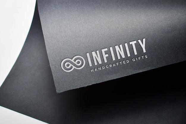 Silbernes logo-modell auf schwarzem papier