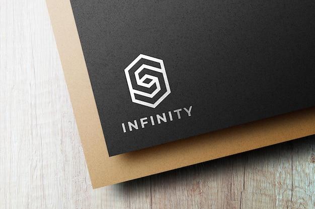Silbernes logomodell auf schwarzem papier