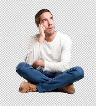 Sitzender junger mann, der sich wundert