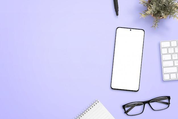 Smartphone mit isoliertem bildschirm für modell auf lila schreibtisch, umgeben von brille, block, pflanze, tastatur und stift. reinigen sie den text nebenan