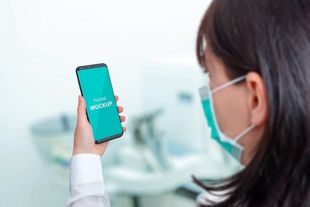 Smartphone-modell im krankenhauslaborkonzept. frau mit maske, die telefon hält