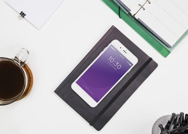 Smartphone-modell mit büromaterialien auf dem tisch