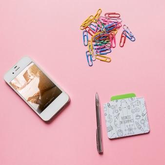 Smartphone-modell mit büromaterialien