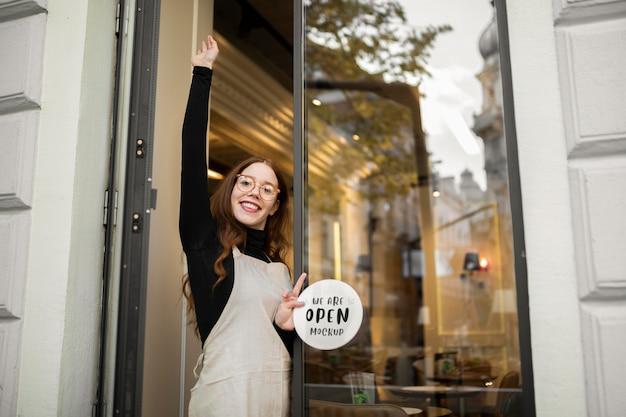 Smiley-frau, die an einem restaurant arbeitet, das neben der tür steht