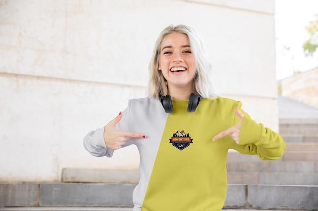 Smiley frau zeigt auf hoodie