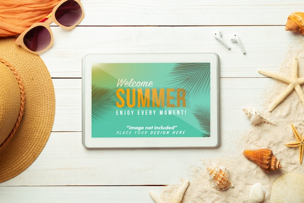 Sommer mit tablet-computer-modellvorlage und strandzubehör auf weißem holz