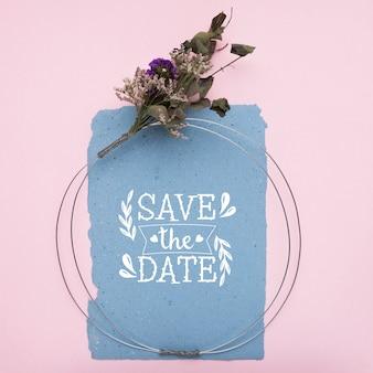 Speichern sie das datumsmodell auf blauem papier und getrockneten blumen