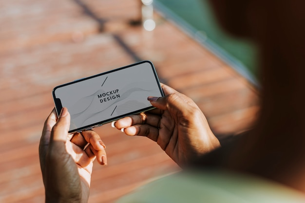 Sportive frau, die ihr telefon in einem park verwendet