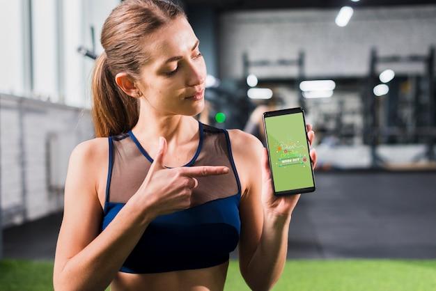 Sportliche frau, die auf smartphonemodell zeigt
