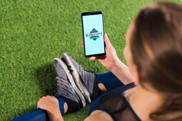 Sportliche frau, die smartphonemodell verwendet