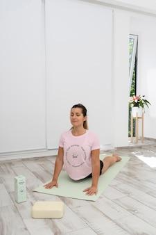 Sportliche frau, die yoga zu hause macht
