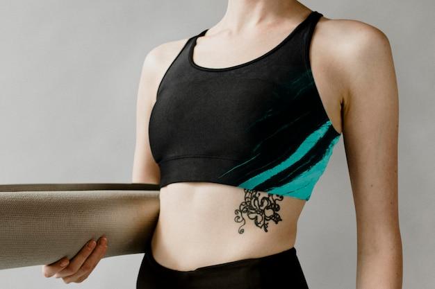 Sportliche frau mit einem yogamatten-modell