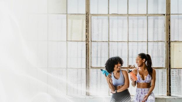 Sportliche frauen, die in einem fitnessstudio sprechen, während sie wassermodell trinken