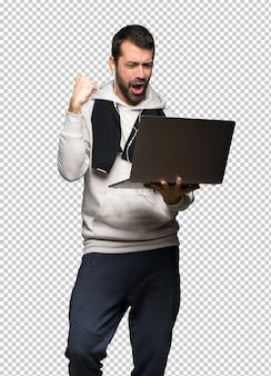 Sportmann, der einen laptop zeigt