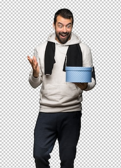 Sportmann, der geschenkbox in den händen hält