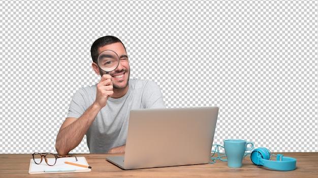 Starker junger mann, der eine lupe auf seinem laptop verwendet