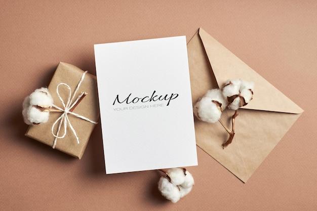 Stationäre einladung oder grußkartenmodell mit umschlag, geschenkbox und natürlichen baumwollpflanzenblumen