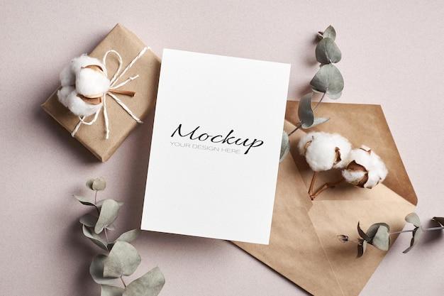 Stationäres modell der einladungs- oder grußkarte mit geschenkbox, trockenem eukalyptus und blumen aus reiner baumwolle