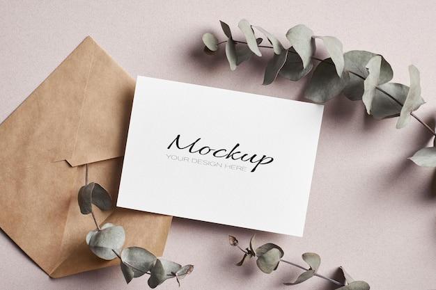 Stationäres modell der einladungs- oder grußkarte mit umschlag und trockenen eukalyptuszweigen
