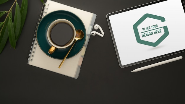 Stilvoller arbeitsbereich mit mockup-tablet, büromaterial und kaffeetasse