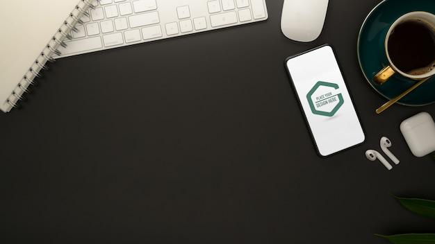 Stilvoller arbeitsbereich mit modell-smartphone, büromaterial und kaffeetasse