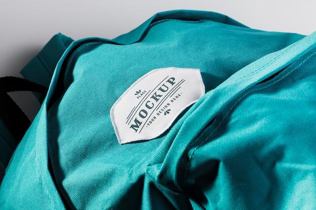 Stoffkleidungs-patch-modell auf blauem rucksack