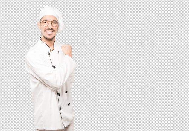 Stolzer junger koch, der mit seinem arm eine geste der stärke tut