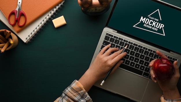 Studentenhand, die einen apfel hält und auf laptop tippt