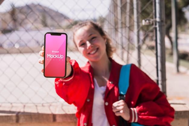 Studentenmädchen, das ihr telefonmodell zeigt