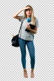Studentenmädchen mit den gläsern, die weit weg mit der hand schauen, um etwas zu schauen