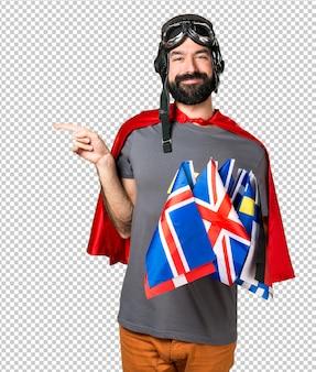 Superheld mit vielen flaggen, die auf den seitenflügel zeigen