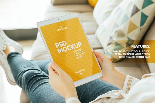 Tablet-bildschirm modell gehalten von einer frau, die auf der couch sitzt