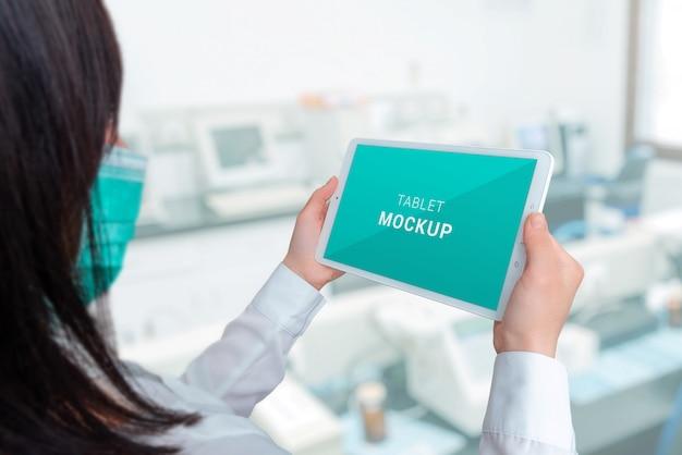 Tablet-modell in den händen eines spezialisten. krankenhauslabor im hintergrund