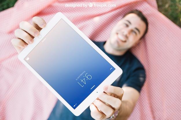 Tablet-modell mit dem mann, der auf stoff liegt