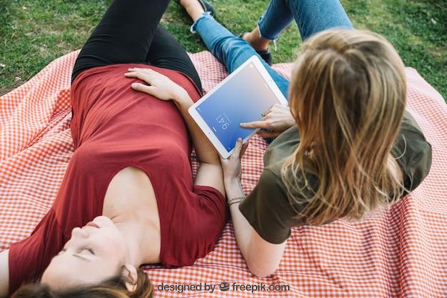 Tablet-modell mit frauen, die ein picknick haben