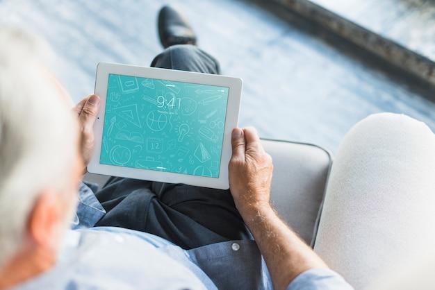 Tablet-modell mit senior für app-präsentation