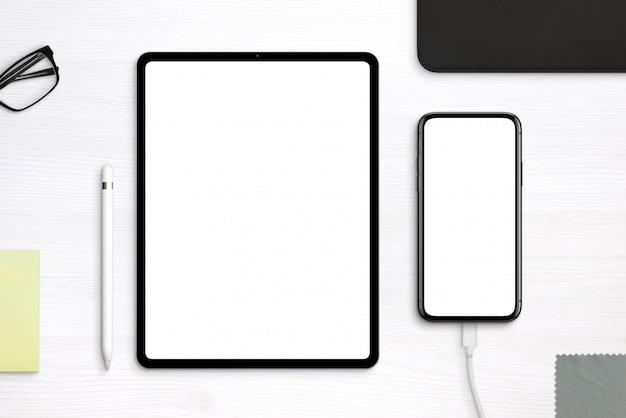Tablet- und telefonmodell auf dem schreibtisch. draufsicht, flache lay-szene mit getrennten ebenen