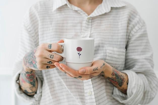 Tätowierte frau mit einer tasse kaffeemodell