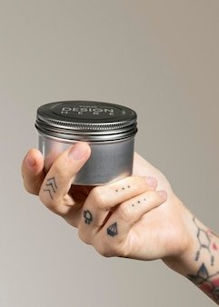 Tätowierte hand hält gesichtscremedose psd-modell