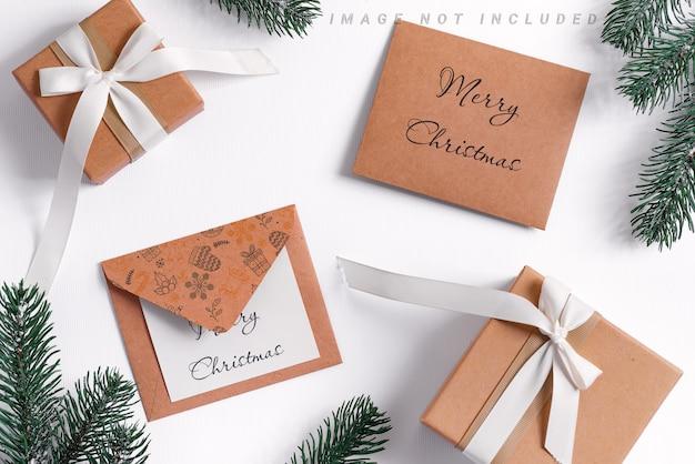 Tannenzweigrahmen mit weihnachtsmodellkarte und umschlägen auf weiß