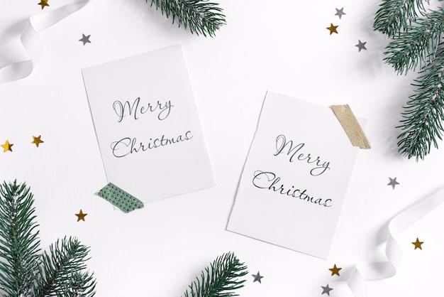Tannenzweigrahmen mit weihnachtsmodellkarten auf weiß
