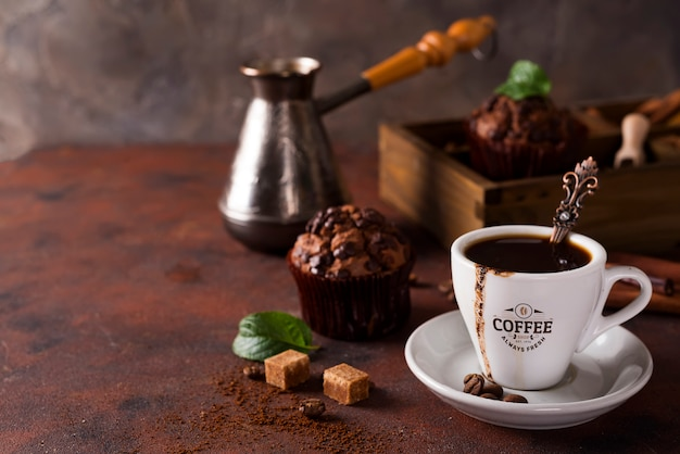Tasse kaffee mit kaffeebohnen, holzkiste mit kaffeekörnern und gewürzen, cupcake auf einem stein