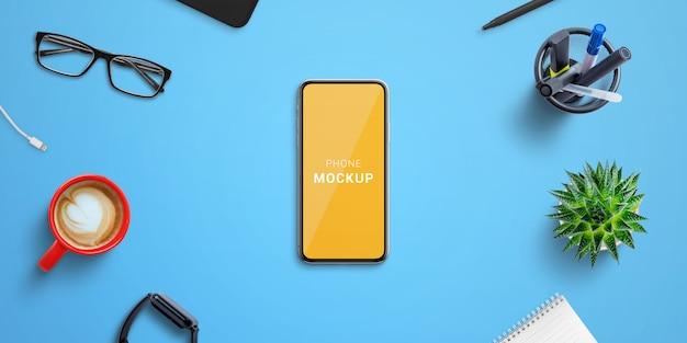 Telefonmodell auf blauem schreibtisch, umgeben von büromaterial. isolierter bildschirm für modell-, website- oder app-präsentation. top vie, flach liegen