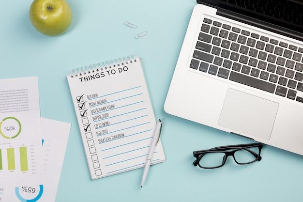 Top view notebook mit täglichen aufgaben und laptop