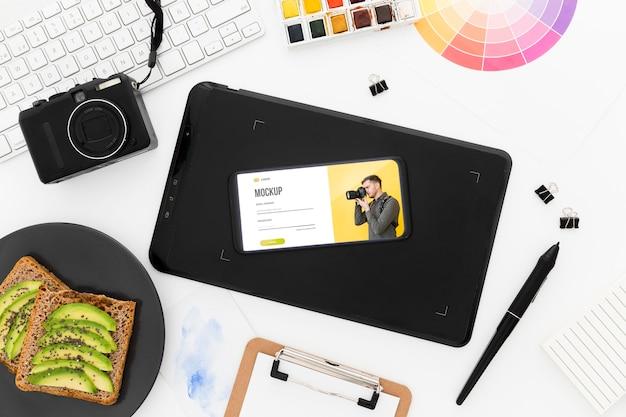 Top view schreibtisch mit telefonmodell und avocado-toast