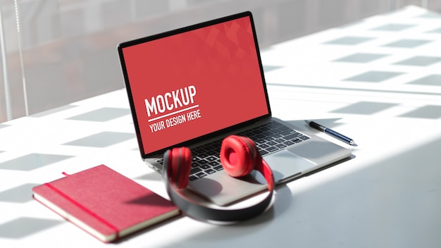 Tragbares laptop-modell im arbeitsbereich mit kopfhörer